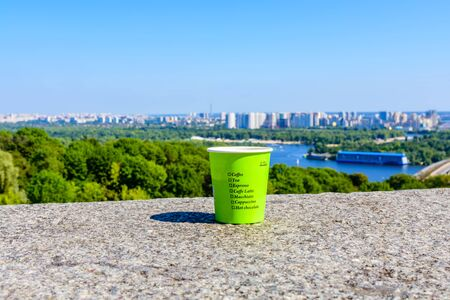 Paper glass of coffee on stone parapet in front of Kiev cityscape. View on residential districts on left bank of river Dnieper in Kiev, Ukraine