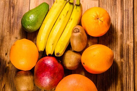 Still life with exotic fruits. Bananas, mango, oranges, avocado, grapefruit and kiwi fruits on rustic wooden table. Top view