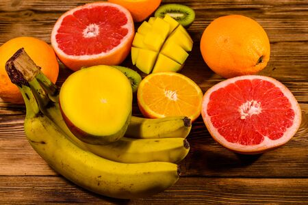 Still life with exotic fruits. Bananas, mango, oranges, grapefruit and kiwi fruits on rustic wooden table
