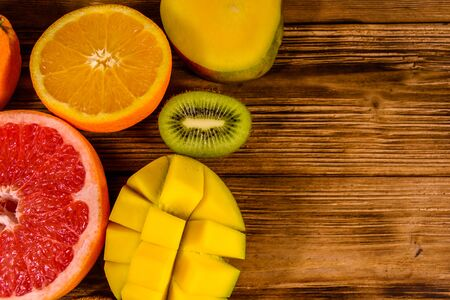 Still life with exotic fruits. Mango, oranges, grapefruit and kiwi fruits on rustic wooden table. Top view