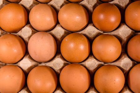 Pile of hen eggs in paper tray on wooden table. Top view