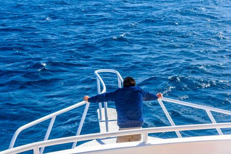 Young man looks on sea from the yacht bow
