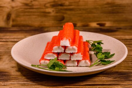 Ceramic plate with pile of crab sticks and parsley twig on wooden table