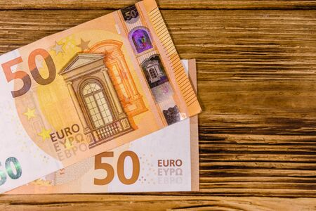 Fifty euro banknotes on rustic wooden background. Top view
