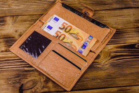 Brown leather wallet with fifty euro banknotes on wooden background 版權商用圖片