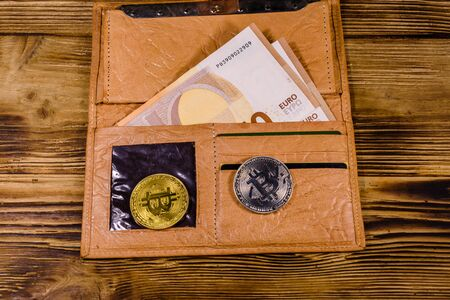 Brown leather wallet with fifty euro banknotes and bitcoins on wooden background Zdjęcie Seryjne