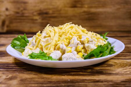 Festive salad with chicken breast, canned pineapple, cheese, sweet corn and mayonnaise on rustic wooden table