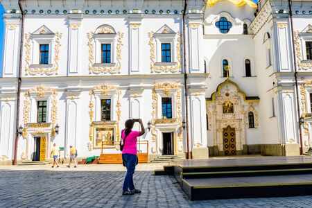 Young woman taking a photo of Dormition Cathedral on her smartphone on territory of Kiev Pechersk Lavra Imagens