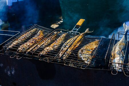 Whole scomber fish cooking in metal grate grill