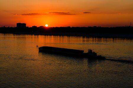 Long heavy barge on Dnieper river near city Kremenchug at sunset Stock fotó