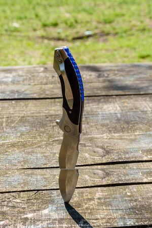 Folding knife stuck in old wooden board