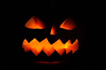 Carved halloween pumpkin jack-o-lantern glows in darkness