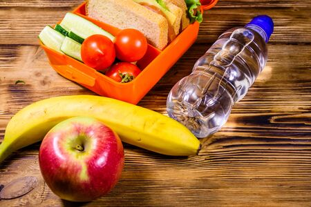 Ripe apple, banana, bottle of water and lunch box with sandwiches, cucumbers and tomatoes on rustic wooden table