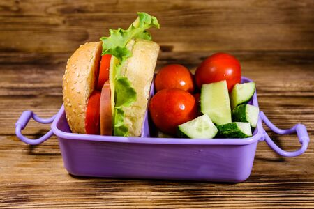 Lunch box with hamburger, cucumbers and tomatoes on rustic wooden table
