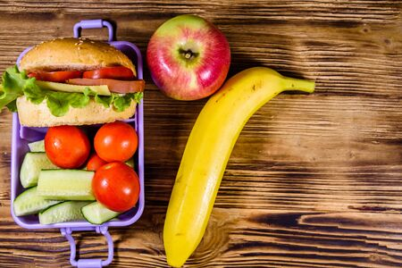 Ripe apple, banana and lunch box with hamburger, cucumbers and tomatoes on rustic wooden table. Top view Stock Photo