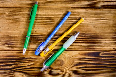 Multi colored ball pens on rustic wooden table. Top view Stok Fotoğraf