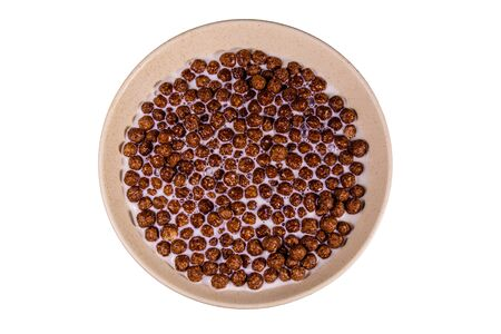 Ceramic plate with chocolate cereal balls in milk isolated on white background