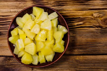 Ceramic plate with chopped canned pineapple on rustic wooden table. Top view
