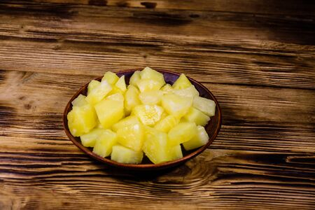 Ceramic plate with chopped canned pineapple on rustic wooden table Zdjęcie Seryjne