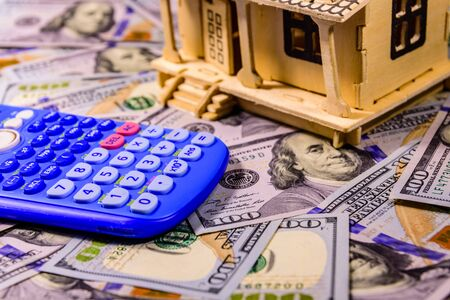 Plywood model of house, calculator and one hundred dollar banknotes. Loan, real estate concept 写真素材