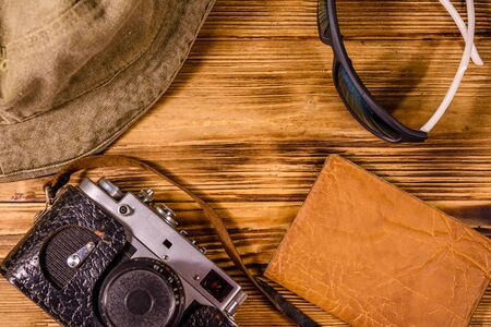 Hipster hat, vintage camera, sunglasses and passport on wooden background. Top view