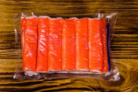 Vacuum pack of crab sticks on wooden table. Top view