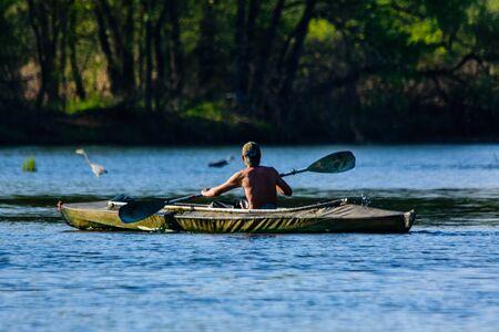 Young man kayaking on river at summer