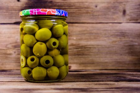 Glass jar with pickled green olives on rustic wooden table