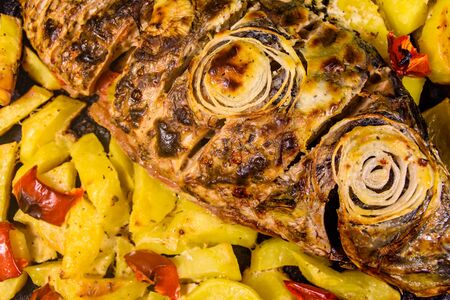 Baked carp fish with potatoes and bell pepper. Top view