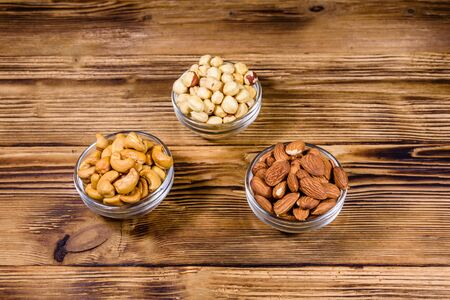 Various nuts (almond, cashew, hazelnut) in glass bowls on wooden table. Vegetarian meal. Healthy eating concept Standard-Bild - 133165969