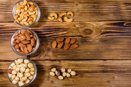 Various nuts (almond, cashew, hazelnut) in glass bowls on wooden table. Vegetarian meal. Healthy eating concept. Top view Standard-Bild - 133167977