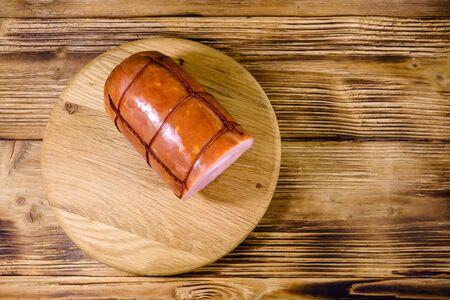 Cutting board with sausage on rustic wooden table. Top view