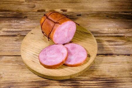 Cutting board with sliced sausage on rustic wooden table Stock Photo