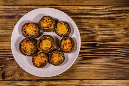Baked champignons stuffed with minced meat and cheese in plate on wooden table. Top view Stock fotó