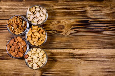 Various nuts (almond, cashew, hazelnut, pistachio, walnut) in glass bowls on wooden table. Vegetarian meal. Healthy eating concept. Top view