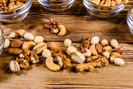 Various nuts (almond, cashew, hazelnut, pistachio, walnut) in glass bowls on wooden table. Vegetarian meal. Healthy eating concept 写真素材