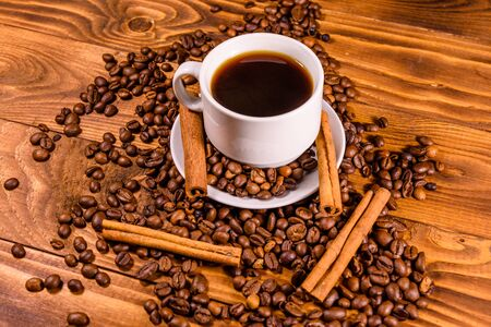 Cup of hot coffee, cinnamon sticks and scattered coffee beans on rustic wooden table