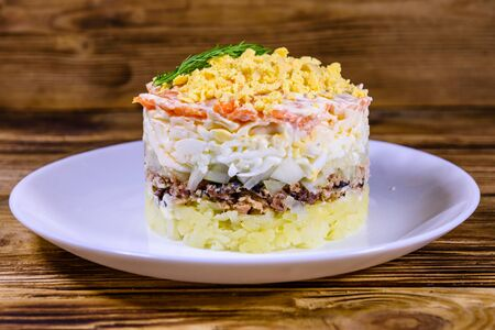 Plate with traditional russian salad Mimosa on wooden table. Layered salad with potatoes, sardine, cheese, carrot, eggs and mayonnaise