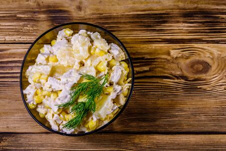 Festive salad with chicken breast, canned pineapple, cheese, sweet corn and mayonnaise on rustic wooden table. Top view