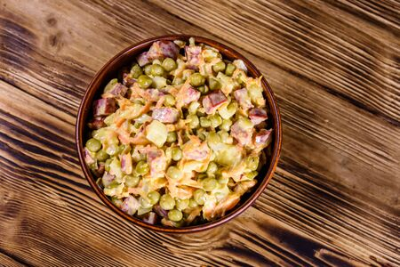 Salad with sausage, green pea, onion and carrot in glass bowl on rustic wooden table. Top view Reklamní fotografie