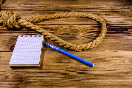 Rope with noose for suicide, blank notepad and pen on wooden background Reklamní fotografie