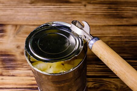 Opening of aluminium tin can with chopped canned pineapple Stock fotó