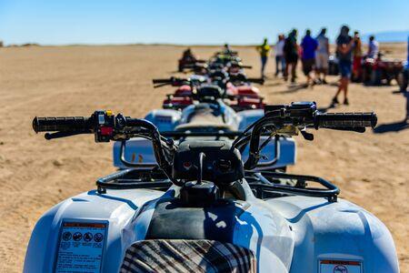 Unrecognizable people near quad bikes during safari trip in Arabian desert not far from Hurghada city, Egypt