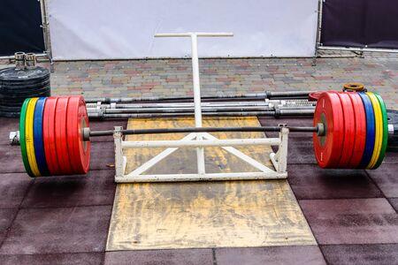 Heavy barbell on platform in street gym