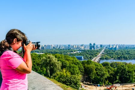 Young woman taking photo of Kiev cityscape and river Dnieper