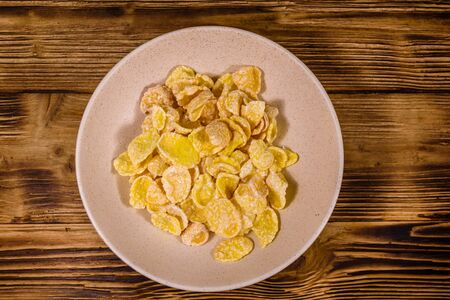 Ceramic plate with cornflakes on a wooden table. Healthy eating. Top view