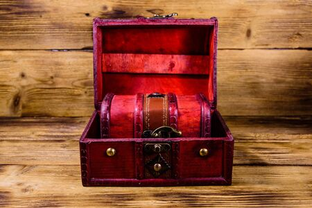 Vintage chest from red wood on rustic wooden background