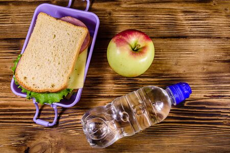 Ripe apple, bottle of water and lunch box with sandwiches on wooden table. Top view Foto de archivo - 138016085