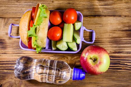 Ripe apple, bottle of water and lunch box with hamburger, cucumbers and tomatoes on rustic wooden table. Top view