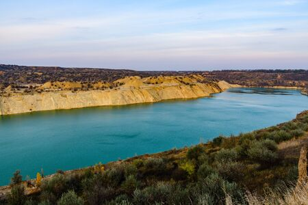 Lake with sandy bank in abandoned coal quarry